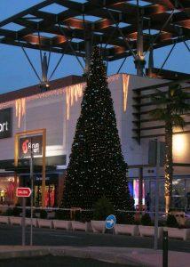 Stor plastgran utomhus med belysning och dekor. Stora julbelysningar på fasaden.