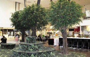 Stora konstgjorda äppelträd i köpcentrum.