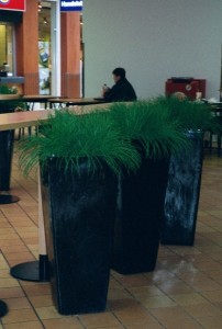 Konstgräs i hög svart kruka.