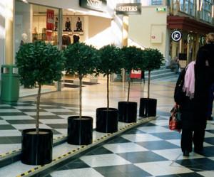 Konstgjorda lagerbollar i svarta krukor i köpcentrum.