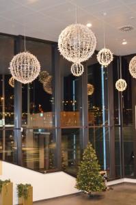 Stora bollar med ledbelysning och julgranar i ett köpcentrum